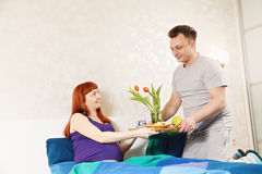 Guy serves breakfast. For pregnant wife to bed Stock Photos