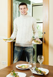 Guy serving festive table with  fish Royalty Free Stock Images