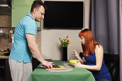 Guy serving lunch to pregnant woman Stock Image