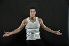 Guy or sexy surprised man with muscular hands. Fashion. guy or sexy surprised man with muscular hands in vest and hat posing in studio on black background Stock Images