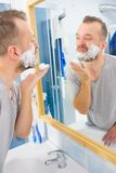 Guy shaving his beard in bathroom royalty free stock photos