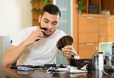 Guy shaving mustache. Guy shaving his mustache electric razor royalty free stock photography