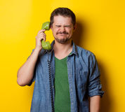 Guy in shirt with green dial phone Royalty Free Stock Photography