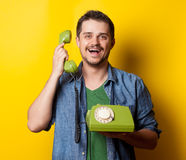 Guy in shirt with green dial phone Royalty Free Stock Photos
