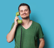 Guy in shirt with green dial phone Royalty Free Stock Images