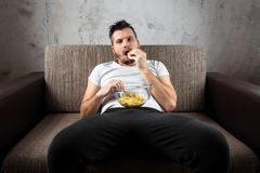The guy in the shirt is lying on the couch, eating chips and watching a sports channel. The concept of laziness. Frustration, procrastination, the person at stock photography