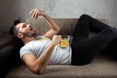 The guy in the shirt is lying on the couch, eating chips and watching a sports channel. The concept of laziness. Frustration, procrastination, the person at royalty free stock photography
