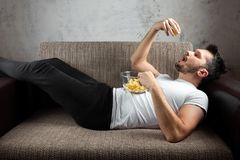 The guy in the shirt is lying on the couch, eating chips and watching a sports channel. The concept of laziness. Frustration, procrastination, the person at royalty free stock photos