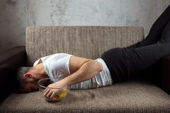 The guy in the shirt is lying on the couch, eating chips and watching a sports channel. The concept of laziness. Frustration, procrastination, the person at royalty free stock photo