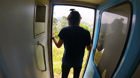 Guy in the shirt rides the train standing at the door. And holds onto the rail in Sri Lanka gopro stock video footage