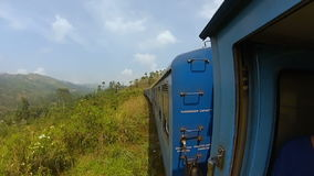 Guy in the shirt rides the train standing at the door. And holds onto the rail in Sri Lanka gopro stock footage