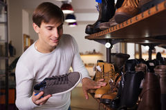Guy in the shoe shop. Guy are looking for a winer shoes in the shoe shop Royalty Free Stock Photography