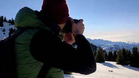 Guy shooting a photo of the mountain landscape in winter. Kazakhstan stock footage