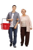 Guy with a shopping basket and a mature woman walking. Full length portrait of a young guy with a shopping basket and a mature women walking towards the camera Royalty Free Stock Images
