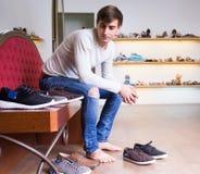 Guy shopping at fashion shoe store. Barefoot guy chooses winter shoes at fashion shoe store stock images