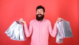 Guy shopping on sales season with discounts. Man with beard and mustache holds shopping bags, red background. Sale and stock photos