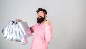 Guy shopping and shows thumbs up gesture. Hipster on happy face recommends to buy. Black friday concept. Man with beard. And mustache carries bunch of shopping stock image