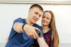 Guy with short haircut in blue T-shirt and girl with dark long hair in red and blue checkered shirt take selfie on the phone stock image
