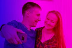 Guy with short haircut in T-shirt and smiling girl with dark long hair in checkered shirt take a selfie on the phone. pink and royalty free stock photography