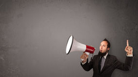 Guy shouting into megaphone. On copy space background Stock Image