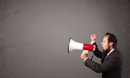 Guy shouting into megaphone. On copy space background Royalty Free Stock Photos