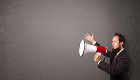 Guy shouting into megaphone on copy space background Stock Photos