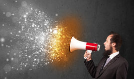 Guy shouting into megaphone and glowing energy particles explode. Concept stock photos