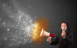 Guy shouting into megaphone and glowing energy particles explode Stock Photo