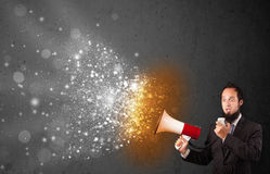 Guy shouting into megaphone and glowing energy particles explode Royalty Free Stock Photography