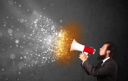Guy shouting into megaphone and glowing energy particles explode Stock Photos