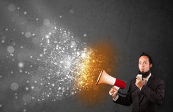 Guy shouting into megaphone and glowing energy particles explode Royalty Free Stock Images