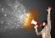 Guy shouting into megaphone and glowing energy particles explode Stock Image