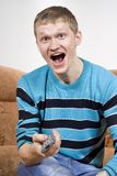 The guy shouts happily, watching tv Royalty Free Stock Photography