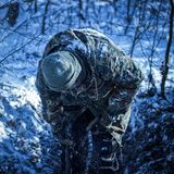 Guy with a shovel in the night winter forest. Guy in camouflage with a shovel in the winter winter forest he bent down and looks for something Stock Photos