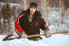 The guy with the shovel throws the snow. The young man relaxes before a shovel of snow on the roof of the cottage Stock Photos