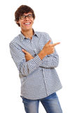 Guy showing forefinger on something. Smiling young man with glasses wearing blue jeans and checkered shirt shows forefinger on something. Isolated on white stock photography
