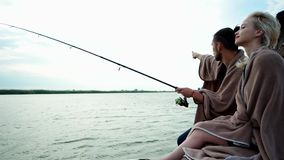 Guy showing his lovely girlfriend beautiful landscape around, sweet couple sitting with rod on dock stock video footage