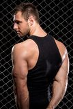 Guy showing his muscles on fence background Stock Photos