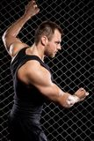 Guy showing his muscles on fence background Royalty Free Stock Images