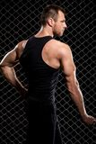 Guy showing his muscles on fence background Royalty Free Stock Photos