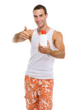 Guy showing sun screen creme and thumbs up Stock Photo