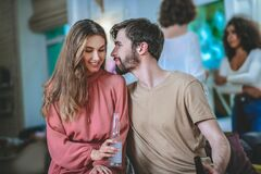 Guy showing sympathy for smiling girl, friends at distance