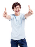 Guy showing thumbs up sign. Young hispanic man wearing glasses, blue t-shirt and jeans showing thumb up hand gesture with both hands and laughing isolated on Stock Images