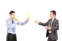 Guy showing a yellow card and blowing a whistle to a young busin Stock Photography