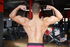 The guy shows the biceps and the inflamed back on the blurred background of the gym. A guy with a bare torso showing biceps and an inflated back on a blurred Royalty Free Stock Images