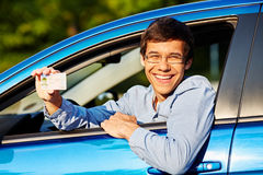 Guy shows driving license from car. Happy young man in glasses showing his driving license from open car window Royalty Free Stock Photography