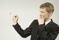 Guy shows something. Handsome guy shows his hand thoughtfully on the background in the studio Stock Image