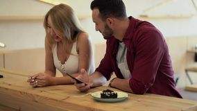 Guy shows something on his phone to the girlfriend. Handsome Man Shows Something On Her Phone To The Girlfriend. Pretty Girl Flirts With Her Boyfriend While He stock footage
