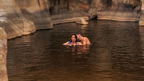 Guy shows to girl to swim in lake created by mountain stream stock video