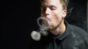 A bearded vaper exhales a smoke ring and through it passes the other, slow motion. The guy shows vaper tricks with steam, slow motion shooting stock video footage